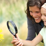 Mother and daughter examining a flower using a magnifying glass